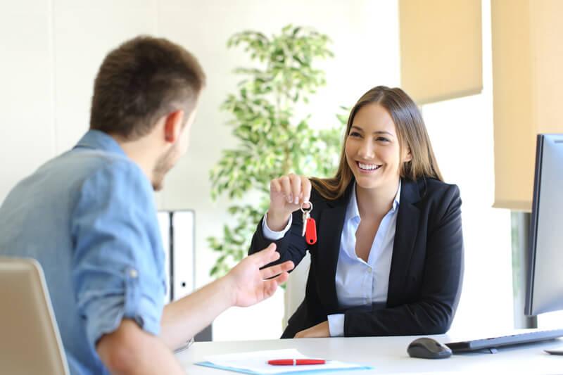 happy female handing rental keys to tenant