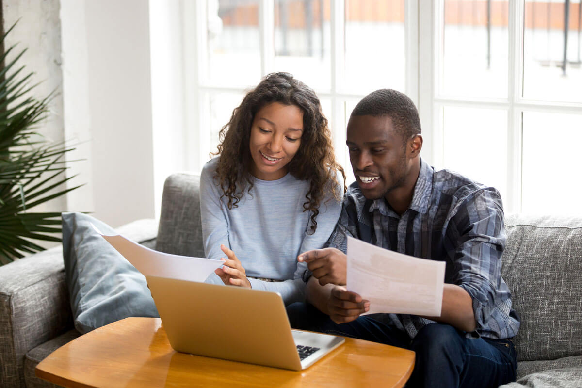 Couple at home checking computer, reviewing documents